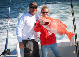 father and daughter fishing trip with a caught redsnapper